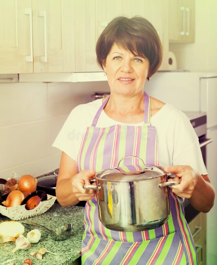 Donna del pensionato che cucina minestra fotografia stock