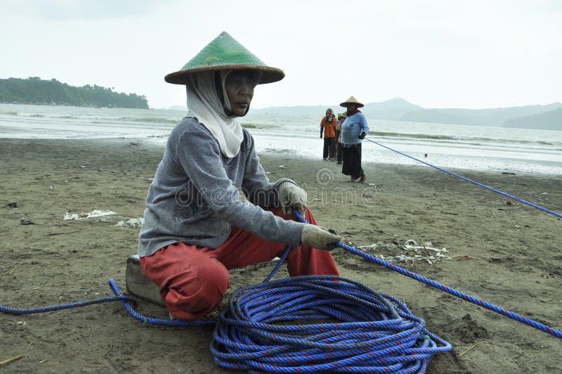 donna del pescatore sul lavoro che tira le reti della corda immagine stock