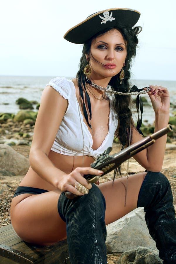 Donna del pirata che si siede vicino al forziere fotografie stock libere da diritti
