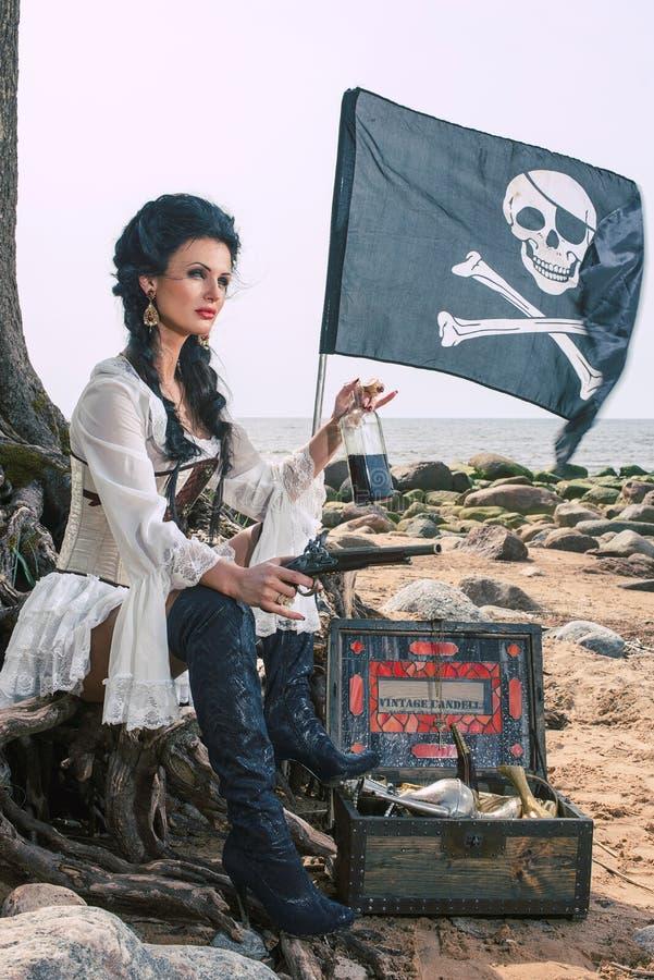 Donna del pirata che si siede vicino al forziere immagini stock