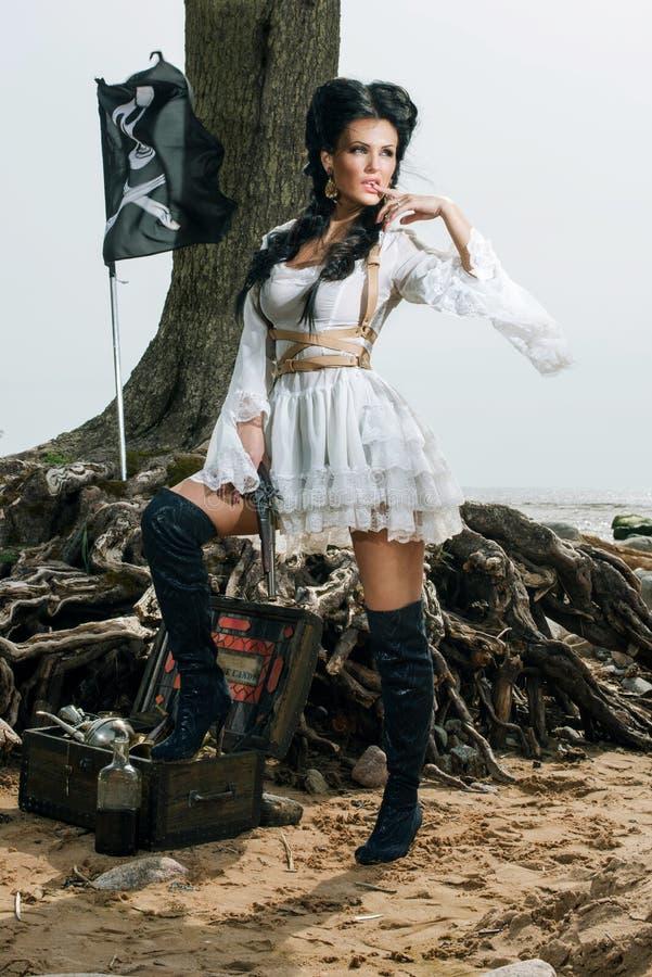 Donna del pirata che sta forziere vicino fotografia stock