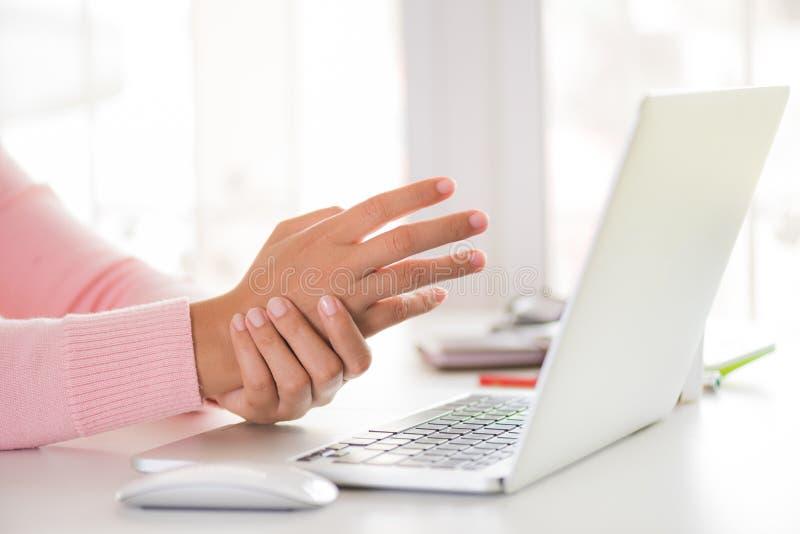 Donna del primo piano che tiene il suo dolore del polso dal per mezzo del computer immagini stock
