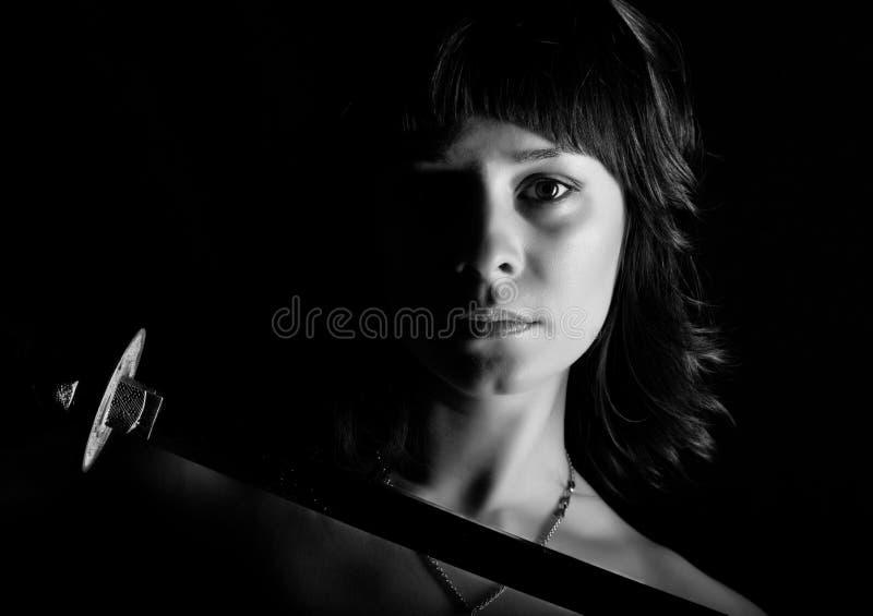 Donna del primo piano con la spada su fondo scuro Rebecca 36 immagine stock libera da diritti