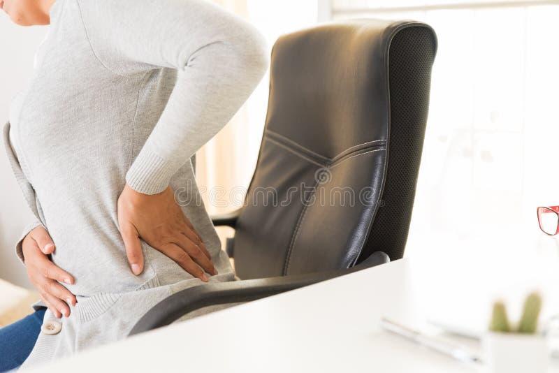 Donna del primo piano con le mani che tengono il suo dolore alla schiena Sindrome dell'ufficio fotografia stock libera da diritti