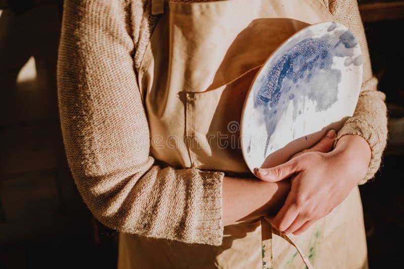 Donna del primo piano in grembiule che tiene il piatto dipinto progettista ceramico fatto a mano delle terraglie fotografia stock libera da diritti