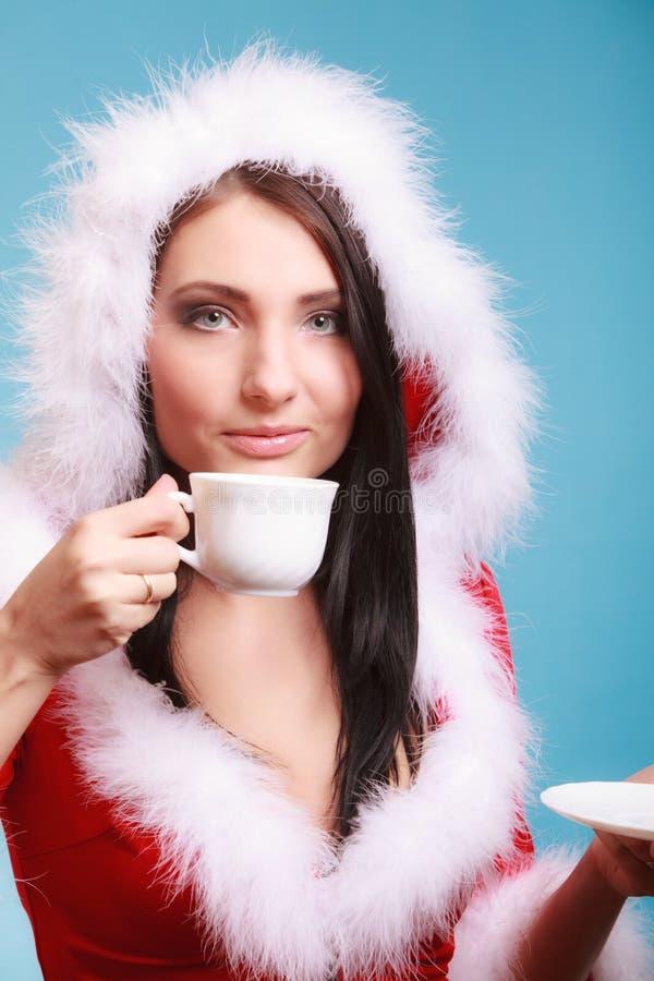 Donna del ritratto che porta il costume del Babbo Natale con la tazza della bevanda calda sul blu fotografia stock libera da diritti