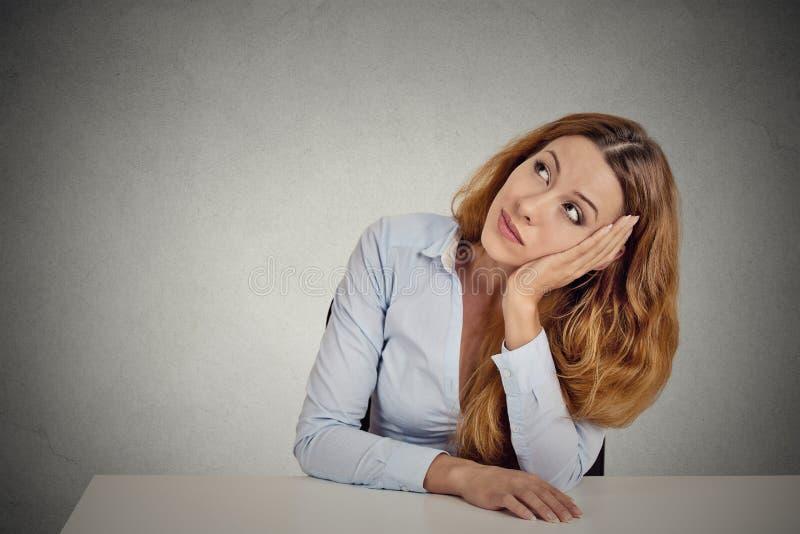 Donna del ritratto che si appoggia uno scrittorio bianco, pensante fotografia stock libera da diritti