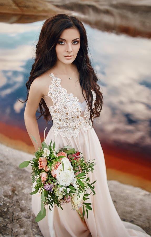 Donna del ritratto con gli occhi azzurri ed il mazzo dei fiori in sue mani sulla natura Capelli splendidi e pelle perfetta immagini stock