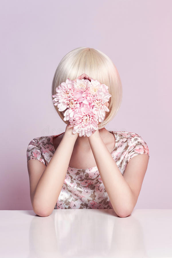Donna del ritratto di arte di modo in vestito e fiori da estate in sua mano con un trucco di contrapposizione luminoso Ragazze cr immagini stock