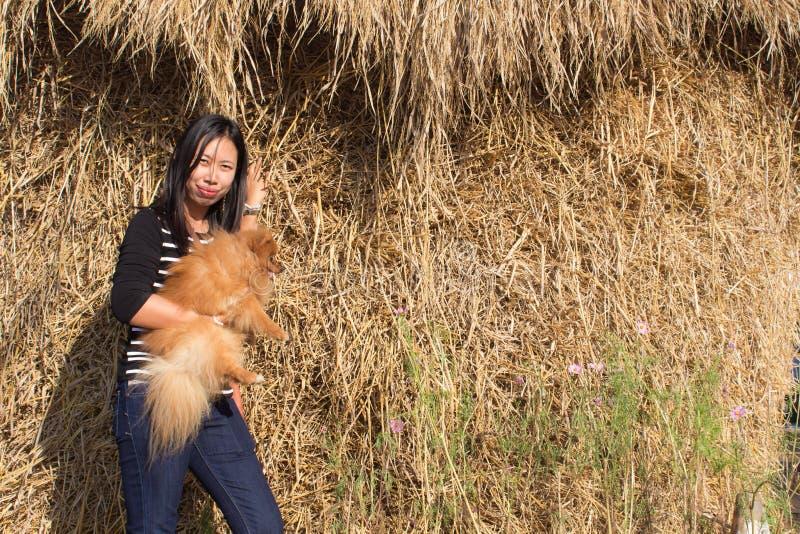 donna del ritratto e pomeranian tailandesi con paglia fotografia stock libera da diritti
