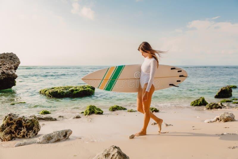 Donna del surfista con il surf Praticando il surfing nell'oceano immagini stock libere da diritti