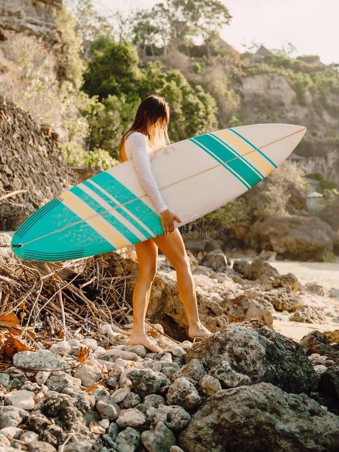 Donna del surfista con il surf Praticando il surfing nell'oceano fotografia stock libera da diritti