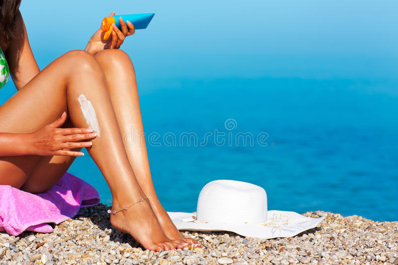 Donna del Tan che applica protezione solare sui suoi piedini immagini stock libere da diritti