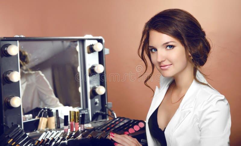 Donna del truccatore di bellezza con i cosmetici dallo specchio nel vestirsi immagine stock