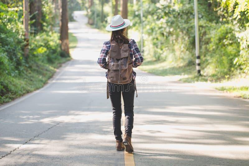 Donna del viaggiatore con lo zaino che gode e che cammina sulla strada in foresta tropicale, Chiang Mai, dao di chiang, viaggio i immagine stock