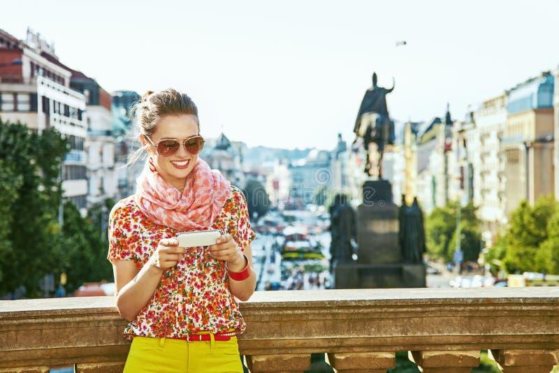 Donna del viaggiatore sul namesti di Vaclavske negli sms di scrittura di Praga fotografie stock