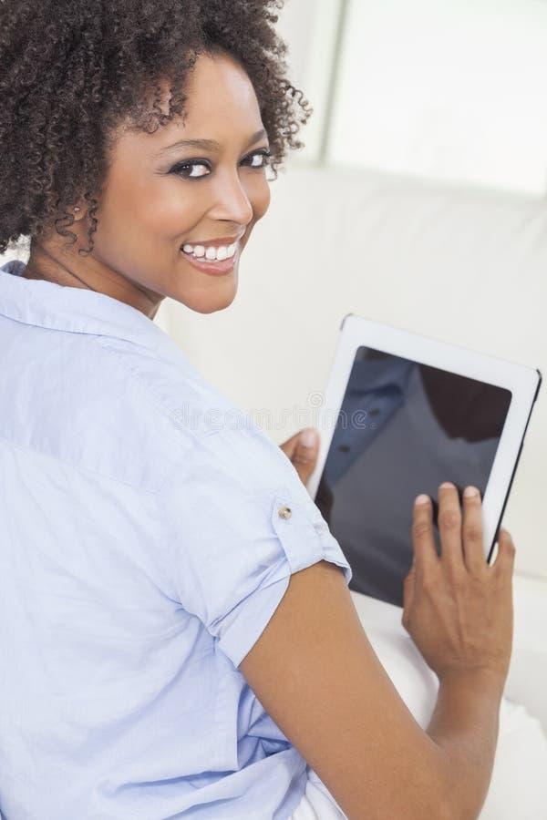Donna dell'afroamericano che per mezzo del calcolatore del ridurre in pani immagini stock libere da diritti