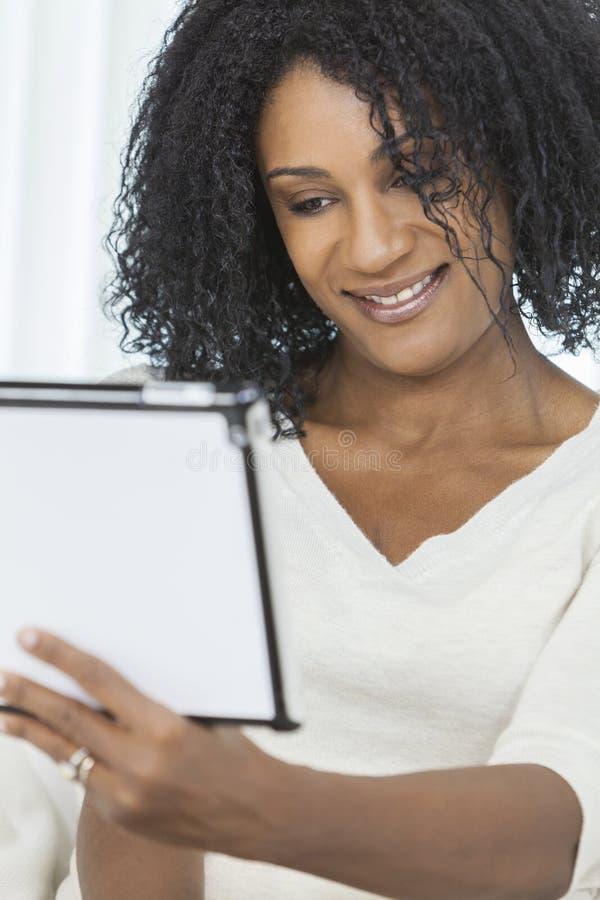 Donna dell'afroamericano che per mezzo del calcolatore del ridurre in pani fotografia stock
