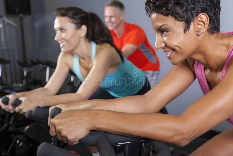 Donna dell'afroamericano sulla bici di esercitazione a ginnastica fotografia stock