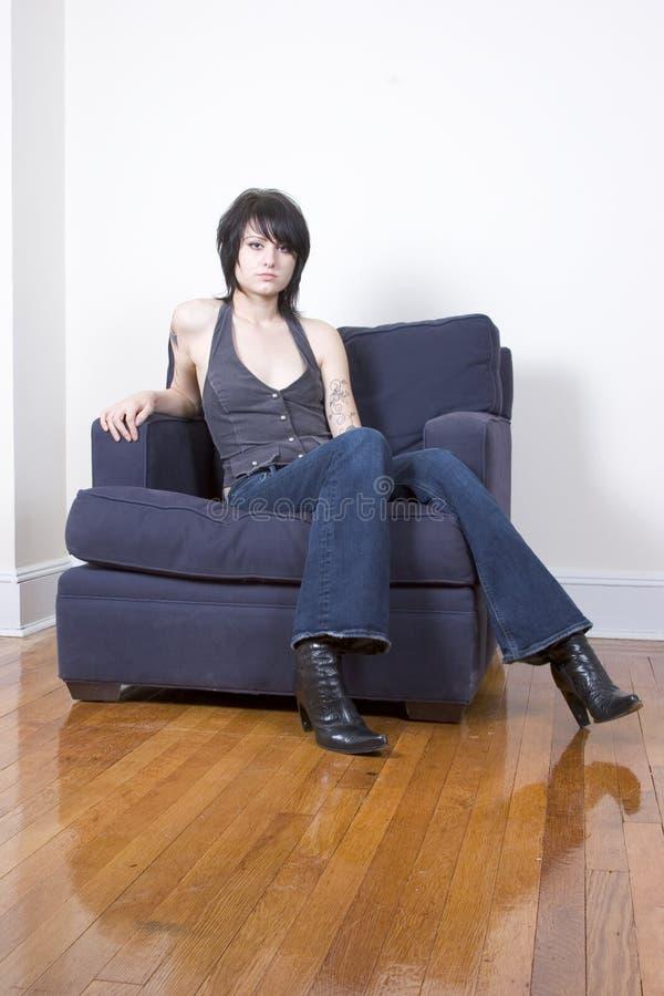 Donna dell'anca che si siede in una presidenza fotografie stock