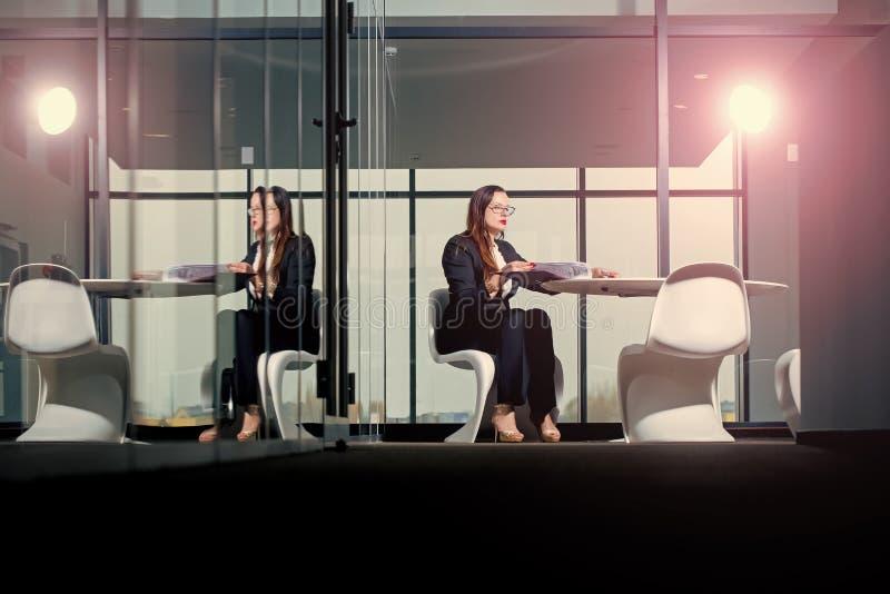 Donna dell'arrivista della donna in attrezzatura convenzionale in ufficio di vetro immagini stock