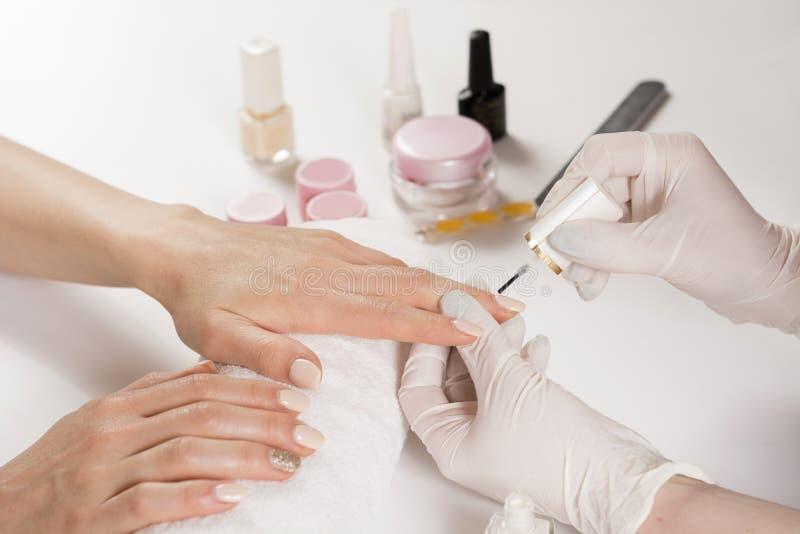 Donna dell'estetista che applica la lucidatura di unghie nello studio del manicure sulla giovane donna immagine stock