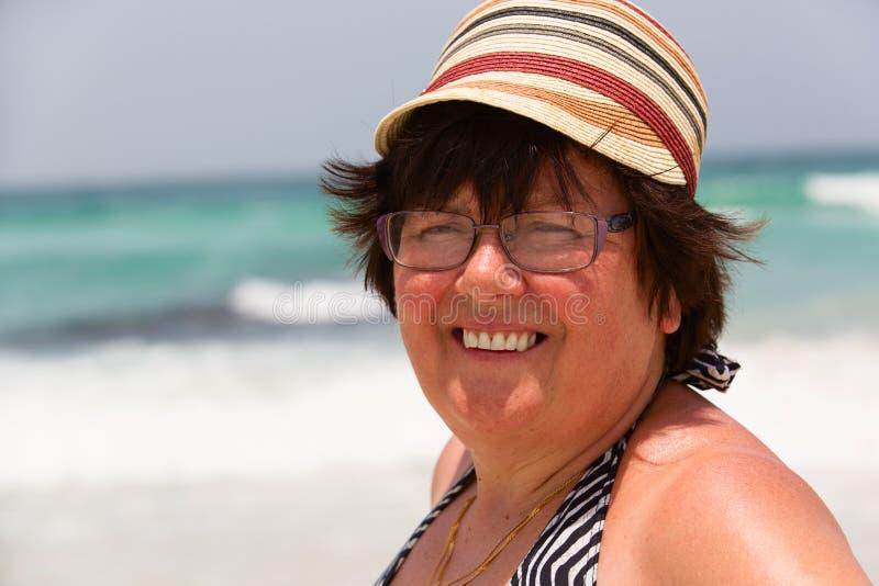 Donna dell'età di pensionamento che riposa sul mare fotografia stock libera da diritti
