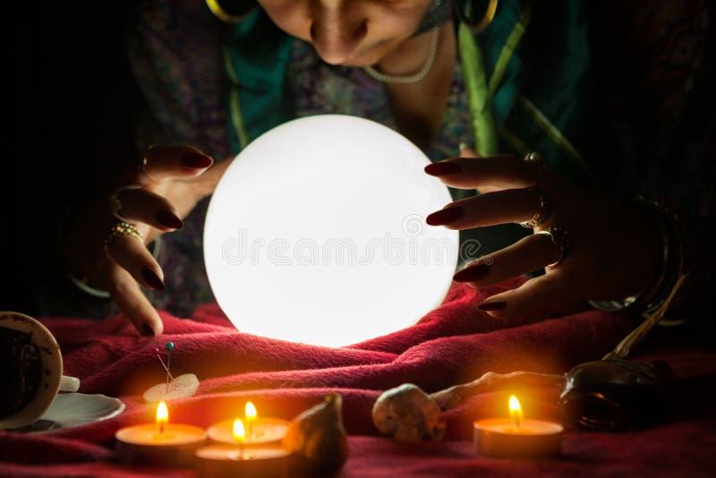 Donna dell'indovino che esamina sfera di cristallo immagini stock
