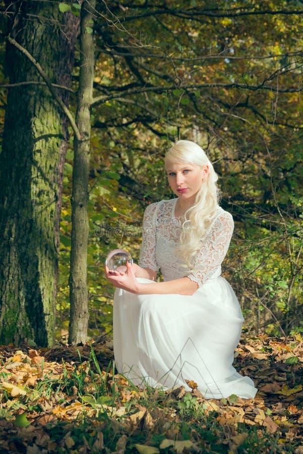 Donna dell'indovino che si siede nel legno fotografia stock libera da diritti
