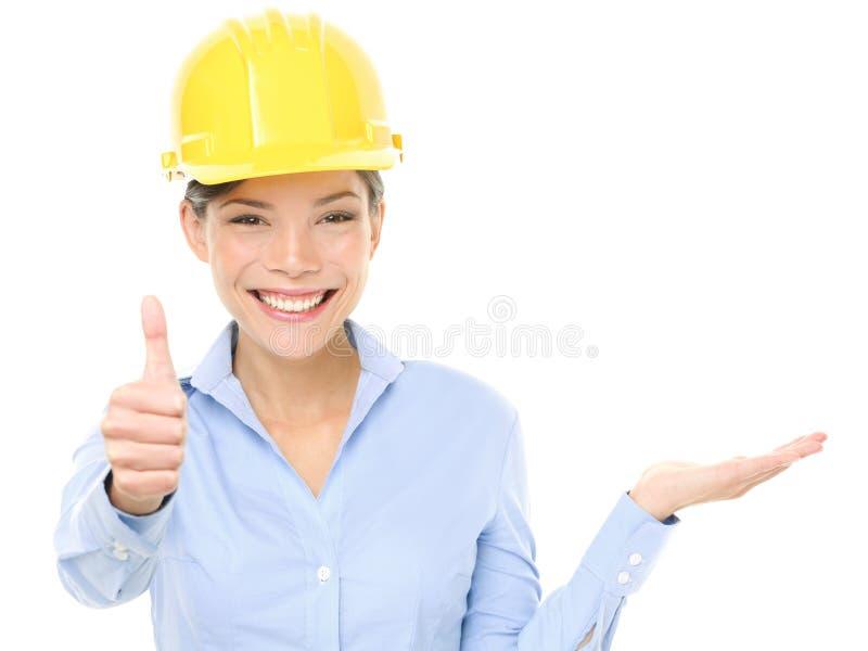 Donna dell'ingegnere che mostra i pollici su e prodotto immagine stock