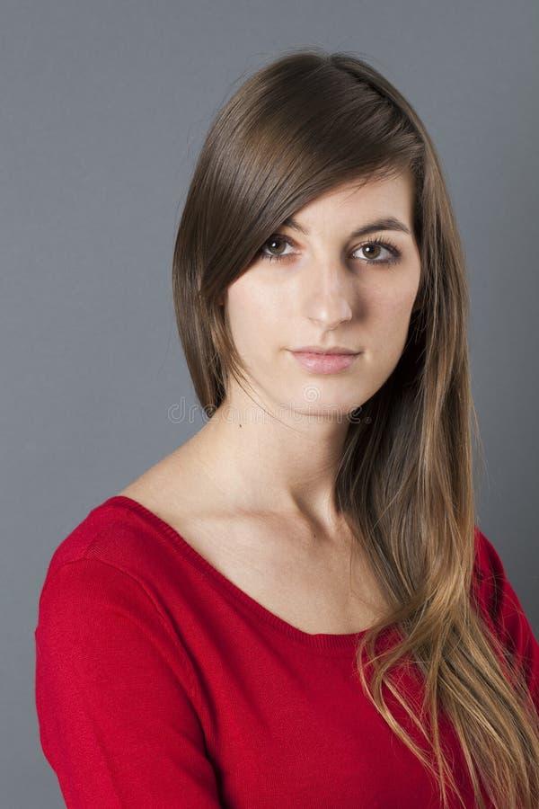 Donna dell'introverso 20s con capelli lunghi che esprimono timidezza fotografie stock