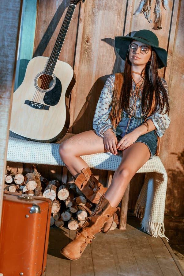 Donna della Boemia attraente che si siede su un banco in casa di legno, chitarra immagini stock libere da diritti