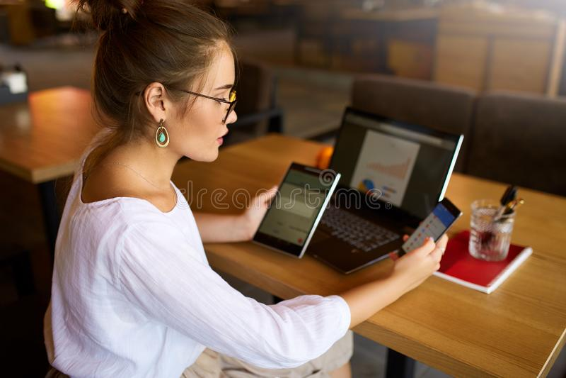 Donna della corsa mista nel funzionamento di vetro con i dispositivi di Internet elettronici multipli La donna di affari delle fr fotografia stock