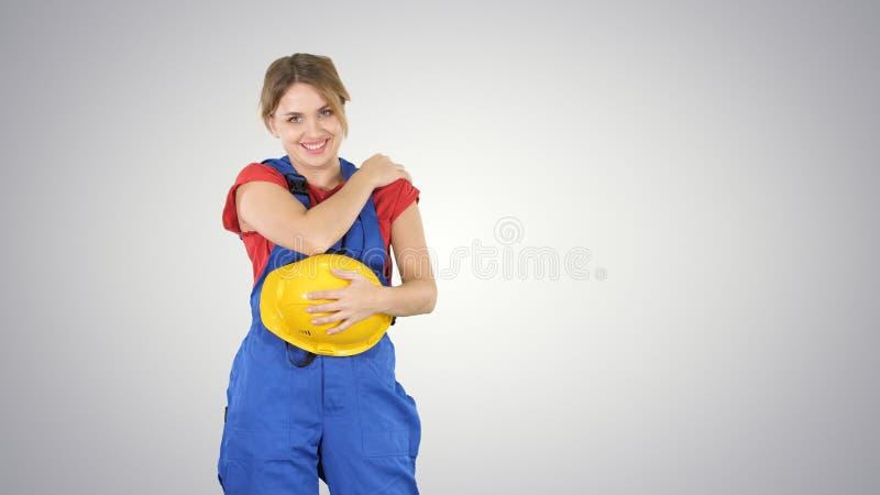 Donna della costruzione che ride di qualcuno dietro la macchina fotografica sul fondo di pendenza fotografie stock libere da diritti