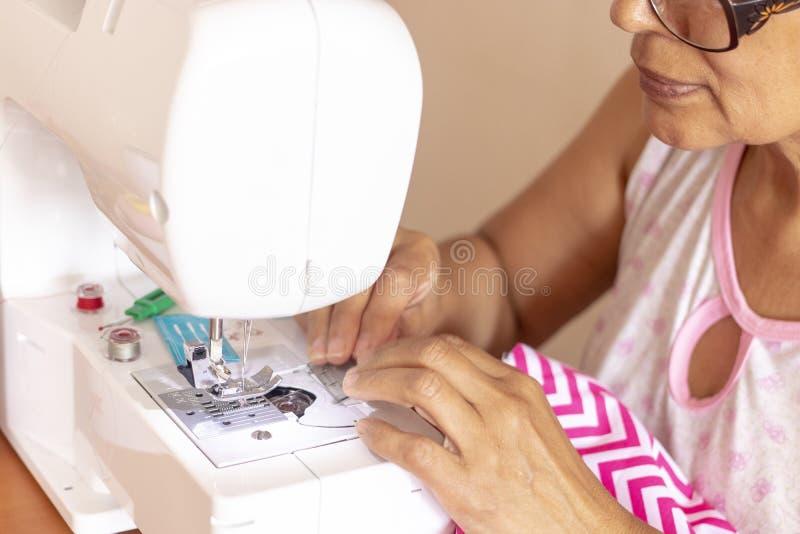Donna della cucitrice che lavora con la sua macchina per cucire fotografia stock