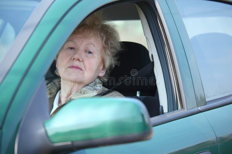 donna della finestra di sguardi s degli anziani dell'automobile fotografia stock