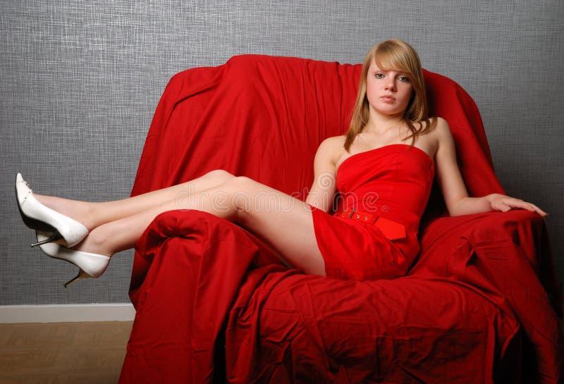Donna della gioventù che siede scompostamente sulla poltrona rossa fotografie stock