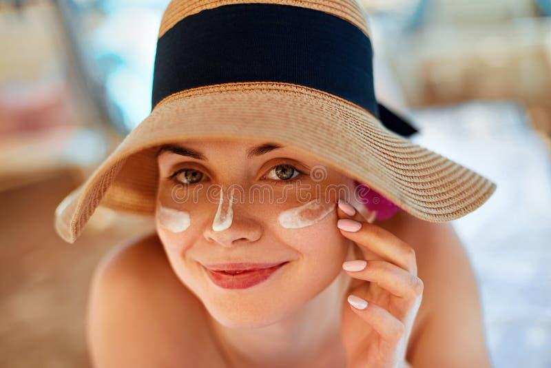 Donna della lozione solare che applica protezione solare Crema femminile del sole della sbavatura sul fronte Skincare fotografie stock