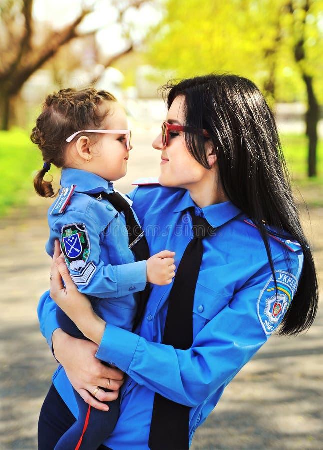 Donna della polizia con sua figlia immagini stock