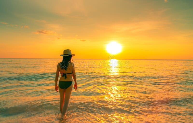 Donna della siluetta che cammina al mare tropicale con il bello cielo di tramonto alla spiaggia di paradiso Bikini di usura della fotografie stock libere da diritti