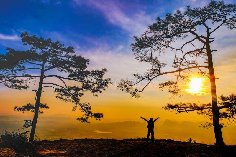 Donna della siluetta sulla scogliera in montagne che esamina tramonto immagine stock libera da diritti
