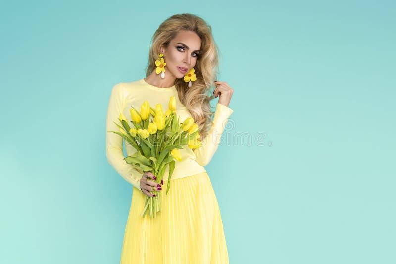 Donna della sorgente Ragazza del modello di estate di bellezza con i vestiti variopinti, tenenti un mazzo dei fiori gialli della  fotografia stock libera da diritti