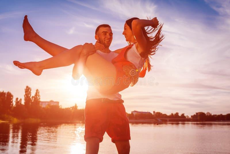 Donna della tenuta del giovane sulla sponda del fiume di estate Coppie divertendosi al tramonto Refrigerazione dei tipi immagini stock