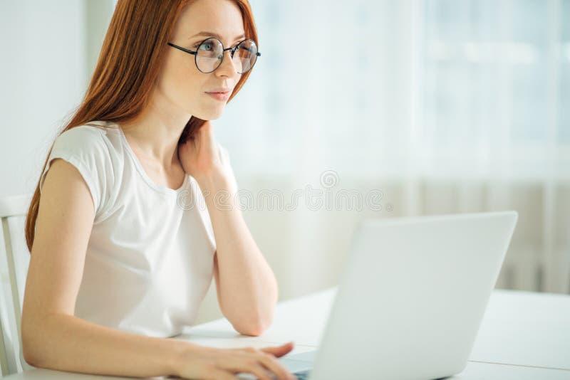 Donna della testarossa che per mezzo del computer portatile Lavorare femminile al computer portatile fotografia stock libera da diritti