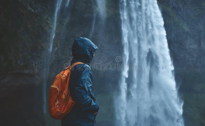 Donna della viandante che cammina sotto la cascata in Islanda immagine stock