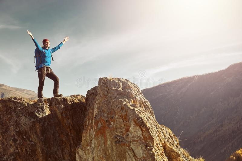 Donna della viandante con lo zaino che sta sopra una montagna con le mani sollevate fotografie stock libere da diritti