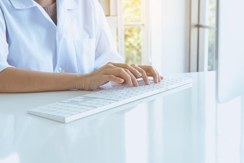 Donna delle mani che utilizza la tastiera di computer sullo scrittorio nella stanza dell'ufficio, fine di battitura a macchina de fotografie stock libere da diritti