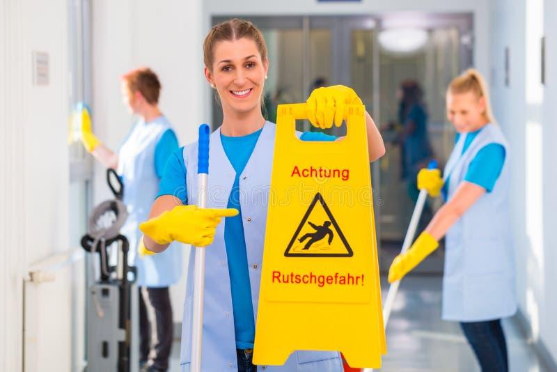 Donna delle pulizie che mostra segnale di pericolo fotografia stock