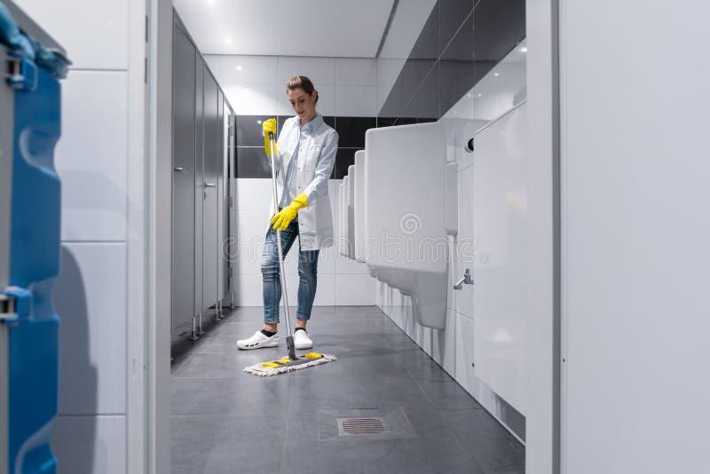 Donna delle pulizie che passa lo straccio sul pavimento nella toilette degli uomini fotografia stock libera da diritti