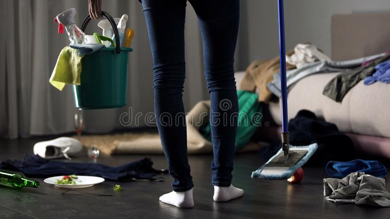 Donna delle pulizie colpita che sta nella camera di albergo sudicia con la zazzera e che lava secchio immagine stock libera da diritti